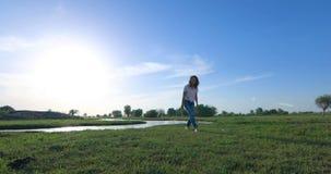 Mujer joven en campo de hierba verde con el río metrajes