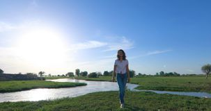 Mujer joven en campo de hierba verde con el río almacen de video