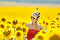 Mujer joven en campo floreciente del girasol Imagenes de archivo