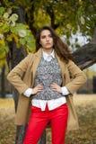 Mujer joven en capa de la moda que camina en parque del otoño foto de archivo