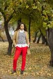Mujer joven en capa de la moda que camina en parque del otoño fotos de archivo libres de regalías
