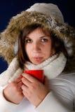 Mujer joven en capa del invierno que bebe el café caliente Fotos de archivo libres de regalías