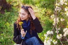 Mujer joven en capa negra que camina en un jardín floreciente de la primavera Imagen de archivo