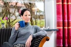 Mujer joven en casa con la taza de coffeee que se relaja Fotografía de archivo libre de regalías