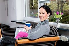 Mujer joven en casa con la taza de coffeee que se relaja Foto de archivo libre de regalías