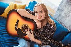 Mujer joven en casa en la afición de la sala de estar que sostiene la guitarra Imagen de archivo
