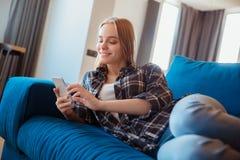 Mujer joven en casa en la sala de estar que miente en smartphone de la ojeada del coche Fotos de archivo