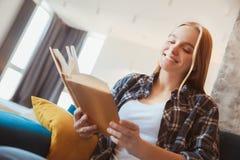 Mujer joven en casa en la sala de estar que se sienta en el primer del libro de lectura del coche Imagen de archivo libre de regalías