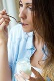 Mujer joven en casa que come el yogur Fotos de archivo