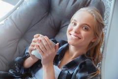Mujer joven en casa que miente en primer de consumición del té de la hamaca fotos de archivo libres de regalías