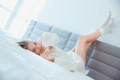Mujer joven en casa que pone las piernas para arriba en la pared en la sonrisa del suéter de la cama que lleva Fotos de archivo
