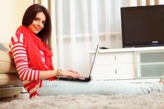 Mujer joven en casa que se sienta con el ordenador portátil Imagenes de archivo