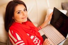 Mujer joven en casa que se sienta con el ordenador portátil Fotografía de archivo