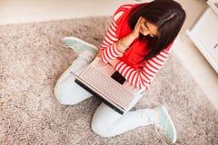 Mujer joven en casa que se sienta con el ordenador portátil en el flo Imágenes de archivo libres de regalías