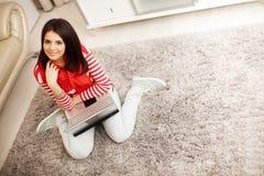 Mujer joven en casa que se sienta con el ordenador portátil en el flo Foto de archivo