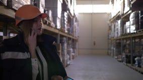 Mujer joven en casco anaranjado en el almacén que habla en el teléfono móvil y que usa una tableta almacen de metraje de vídeo