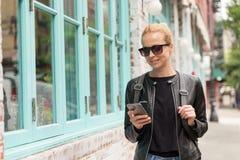 Mujer joven en chaqueta de cuero negra y ocupado de moda con su teléfono móvil mientras que camina una calle de la ciudad Fotografía de archivo