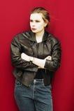 Mujer joven en chaqueta de cuero negra y vaqueros Fondo rojo, Imagenes de archivo