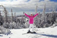 Mujer joven en chaqueta de esquí rosada con los esquís en sus pies que sostienen el esquí fotografía de archivo libre de regalías