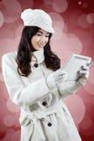 Mujer joven en chaqueta del invierno con la tableta Fotos de archivo libres de regalías
