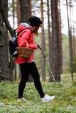 mujer joven en chaqueta roja que disfruta de la naturaleza en el bosque Letonia Fotografía de archivo
