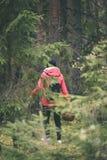 mujer joven en chaqueta roja que disfruta de la naturaleza en el bosque Letonia - VI Imagenes de archivo