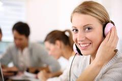 Mujer joven en clase con los auriculares Imagen de archivo libre de regalías