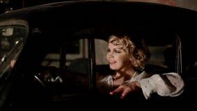 Mujer joven en coche retro dentro almacen de video
