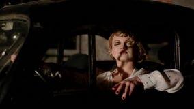 Mujer joven en coche retro dentro almacen de metraje de vídeo