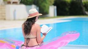 Mujer joven en colchón de aire del bikini en la piscina grande metrajes
