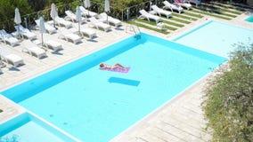 Mujer joven en colchón de aire del bikini en la piscina grande almacen de metraje de vídeo