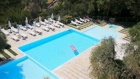 Mujer joven en colchón de aire del bikini en la piscina grande almacen de video