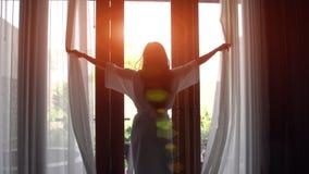 Mujer joven en cortinas abiertas de la albornoz y estiramiento que se coloca cerca de la ventana en casa imagen de archivo libre de regalías
