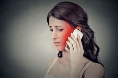 Mujer joven en cuestión que habla en el teléfono móvil que tiene dolor de cabeza del dolor Foto de archivo