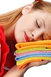 Mujer joven en delantal rojo que duerme en la pila de toallas de té coloridas Fotografía de archivo libre de regalías
