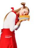 Mujer joven en delantal rojo que duerme en la pila de toallas de té coloridas Foto de archivo