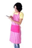 Mujer joven en delantal rosado usando el ordenador de la tablilla Foto de archivo
