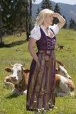 Mujer joven en dirndl en la granja imagen de archivo