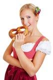 Mujer joven en dirndl que muerde en pretzel Foto de archivo libre de regalías