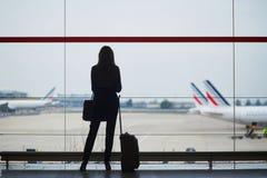 Mujer joven en el aeropuerto, mirando a través de la ventana los aviones Fotografía de archivo libre de regalías