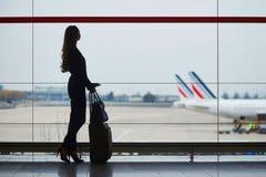 Mujer joven en el aeropuerto, mirando a través de la ventana los aviones Fotos de archivo