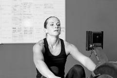 Mujer joven en el aparato de remar - entrenamiento del crossfit Foto de archivo libre de regalías