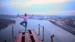 Mujer joven en el asana derecho al borde del puente, práctica de la yoga, adrenalina almacen de video