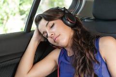 Mujer joven en el asiento trasero del coche, dormido con los auriculares encendido Imagen de archivo