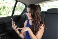 Mujer joven en el asiento trasero del coche que sonríe y que lee el ebook Imagenes de archivo