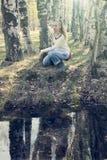 Mujer joven en el banco del lago del bosque, entonando Imágenes de archivo libres de regalías