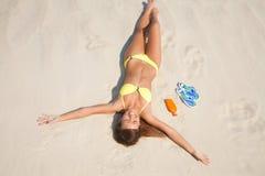 Mujer joven en el bikiní que asolea en la playa Imagen de archivo libre de regalías