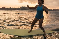 Mujer joven en el bikini brillante que practica surf en un tablero en el océano Foto de archivo libre de regalías