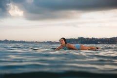 Mujer joven en el bikini brillante que practica surf en un tablero en el océano Imagenes de archivo