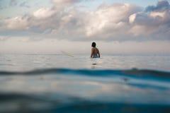 Mujer joven en el bikini brillante que practica surf en un tablero en el océano Fotos de archivo